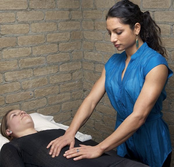 A woman in a blue dress perform osteopathy