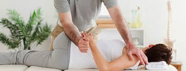 a chiropractor gently twists a womans arm