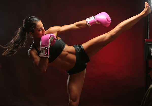 A fit woman performs a high kick wearing pink boxing gloves